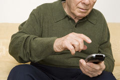 Elderly man using remote control Royalty Free Stock Images