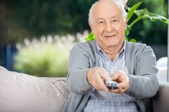 Elderly Man Using Remote Control While Sitting On Stock Photo