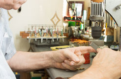 Elderly man using a small electric bench grinder Stock Photography