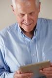 Elderly man using tablet. Laughing Stock Image