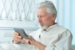 Elderly man using a tablet computer Stock Image