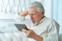 Elderly man using a tablet computer. Portrait of an elderly man using a tablet computer Royalty Free Stock Photo