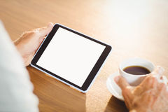 Elderly man using tablet and drinking coffee. At home Stock Photography