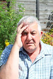 Elderly man very worried and stressed. A closeup of an elderly man with his hand to his head because he is very worried and stressed Stock Image