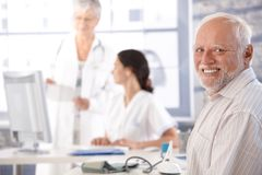 Elderly man waiting for examination smiling Stock Image