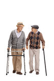 Elderly man with walker and another man with cane walking Royalty Free Stock Photography