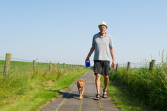 Elderly man walking the dog. Elderly man with straw hat walking the dog in summer season stock photos