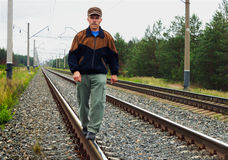 An elderly man walking on tracks Royalty Free Stock Photography