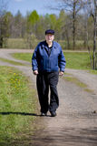 Elderly man walking on road Stock Images
