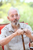 Elderly man with walking stick sitting in garden Stock Images