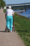 Keeping Active is Key to Senior Health. Old man walking slowly with a red walker next to river on a sunny summers day Stock Image