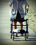 Elderly man walking with Walker on the beach Royalty Free Stock Photo