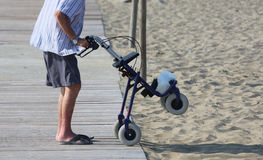 Elderly man walking with Walker on the beach in summer Stock Photos
