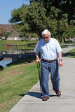 Elderly man walks with a cane Stock Images