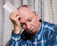 Elderly man wants to take a pill Stock Photo