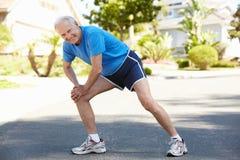 Elderly man warming up for run. Elderly men warming up for run royalty free stock images