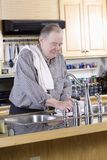 Elderly man washing dishes Royalty Free Stock Photos