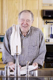 Elderly man washing dishes Royalty Free Stock Images