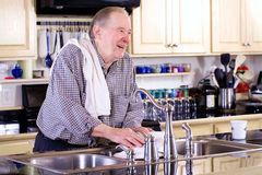 Elderly man washing dishes Stock Photos