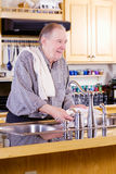 Elderly man washing dishes Stock Photography
