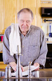 Elderly man washing dishes Royalty Free Stock Photo
