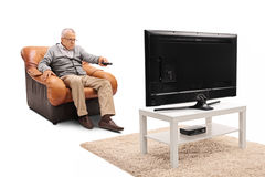 Elderly man watching tv. Frustrated elderly man watching tv and changing channels isolated on white background Stock Photo