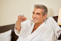 Elderly man watching TV in hotel room Stock Photography