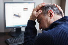 Elderly man wearily turns his head away from the monitor. Stock Photography