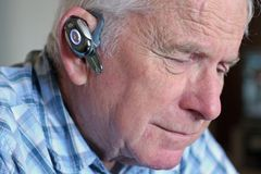 Elderly man wearing hands-free cell phone device Royalty Free Stock Images