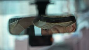 Elderly man wearing hat and looking in rear view car mirror, driver close-up. Stock footage stock video