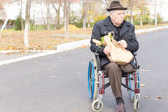 Elderly man in a wheelchair doing grocery shopping. Elderly man in a wheelchair bring home the groceries from the supermarket in a brown paper bag as he sits stock photography