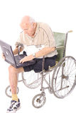 Elderly man in wheelchair on laptop vertical. Isolated on white Royalty Free Stock Photo