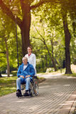 Elderly man on wheelchair with nurse outdoor Royalty Free Stock Images