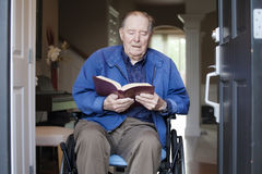Elderly man in wheelchair reading the Bible Stock Photography
