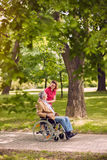 Elderly man in wheelchair talking with daughter in the park- hap. Smiling elderly men in wheelchair talking with daughter in the park- happy family time Stock Photos