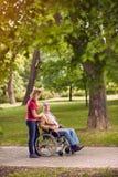 Elderly man in wheelchair talking with daughter in the park. Smiling elderly men in wheelchair talking with daughter in the park Royalty Free Stock Image