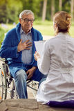 Elderly man in wheelchair who don`t feel good with nurse. Elderly men in wheelchair who don`t feel good with nurse outdoor Stock Images