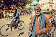 Elderly man with white beard standing with bicycle on the busy street of Varanasi indian city. VARANASI, INDIA - JAN 1: Elderly man with white beard standing Stock Images