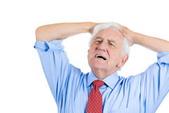 Elderly man with white hair in blue shirt and red tie, stressed and frustrated Royalty Free Stock Photo