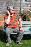 An elderly man with wireless headphones. Stock Photo