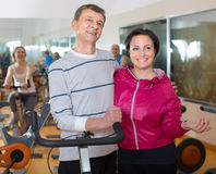 Elderly man and woman in background bikes at the gym Royalty Free Stock Images