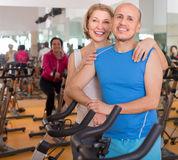 Elderly man and woman in background bikes at the gym Stock Image