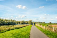Elderly man and woman cycling on a bike path at the top of a dik. Older man and woman cycle on a curved cycle path on a on the edge of the Dutch National Park De royalty free stock image
