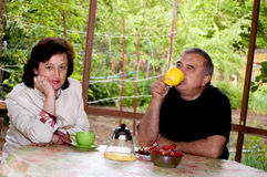 Elderly man and the woman drink tea at outdoors. Stock Images
