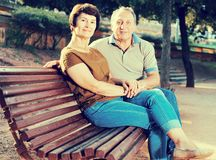 Elderly man and woman embracing on bench. Elderly men and women embracing on park bench stock photos
