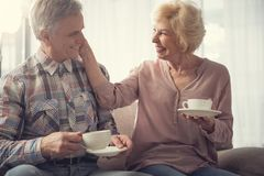 Elderly man and woman enjoying time together in retirement. Smiling senior couple relaxing with cups in arms and staring at one another with amour. Female person Royalty Free Stock Images