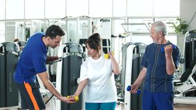Elderly man and woman at gym. Young trainer helping to senior woman lifting dumbbell. Sport and healthcare stock video