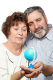 Elderly man and woman look at small globe Stock Photo