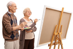 Elderly man and woman painting on a canvas with paintbrushes. Elderly men and women painting on a canvas with paintbrushes isolated on white background royalty free stock images
