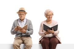 Elderly man and woman reading books. Elderly men and women reading books isolated on white background stock photography